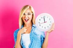 Женщина держа часы показывая почти 12 Стоковое фото RF