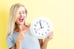 Женщина держа часы показывая почти 12 Стоковые Изображения