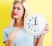 Женщина держа часы показывая почти 12 Стоковое Фото