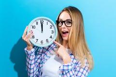 Женщина держа часы показывая почти 12 Стоковые Изображения RF