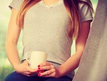 Женщина держа чашку горячего питья, отсутствие стороны Стоковые Фотографии RF