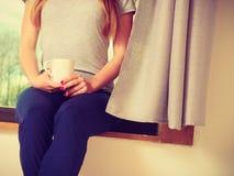 Женщина держа чашку горячего питья, отсутствие стороны Стоковое Изображение