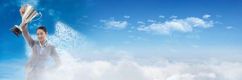 Женщина держа чашку трофея в торжестве в переходе облака неба стоковые изображения