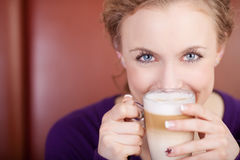Женщина держа чашку Latte кафа в кофейне Стоковая Фотография