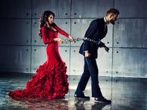 Женщина держа человека на тяжелой цепи Стоковое фото RF