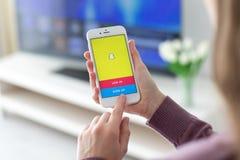 Женщина держа iPhone с социальным обслуживанием Snapchat сети дальше стоковые фото
