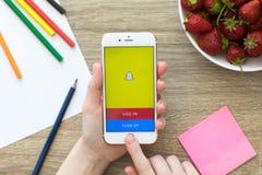 Женщина держа iPhone с социальным обслуживанием Snapchat сети дальше стоковое изображение rf