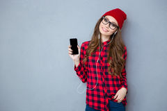 Женщина держа smartphone и слушая музыку в наушниках стоковая фотография rf
