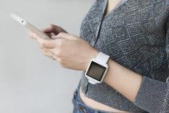 Женщина держа smartwatch мобильного телефона нося Стоковое фото RF