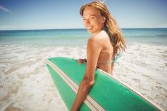 Женщина держа surfboard на пляже Стоковое Изображение RF