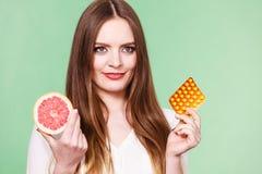 Женщина держит Витамин C пакета грейпфрута и волдыря пилюлек Стоковые Изображения