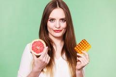 Женщина держит Витамин C пакета грейпфрута и волдыря пилюлек Стоковые Изображения RF