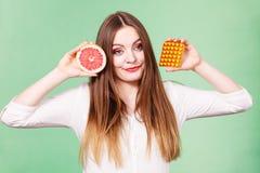 Женщина держит Витамин C пакета грейпфрута и волдыря пилюлек Стоковая Фотография RF
