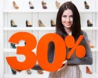 Женщина держит модель продажи 30% на обуви Стоковые Изображения