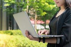Женщина держит портативный компьютер к занимаясь серфингом интернету Стоковое Фото