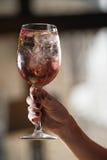 Женщина держит расслабляющий спиртной розовый коктеиль с розой на верхней части Стоковые Изображения