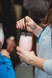 Женщина держит розовый свежий коктеиль в баре Стоковые Фото