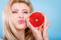 Женщина держит цитрусовые фрукты грейпфрута в руках Стоковое Изображение RF