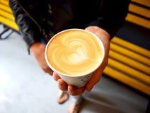 Женщина держит чашку кофе с сердцем Стоковые Изображения