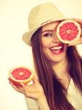 Женщина держит 2 halfs цитрусовых фруктов грейпфрута в руках Стоковая Фотография