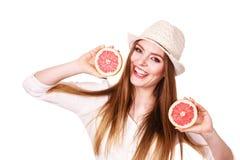 Женщина держит 2 halfs цитрусовых фруктов грейпфрута в руках Стоковое Фото