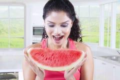 Женщина есть арбуз дома Стоковая Фотография