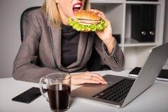 Женщина есть бургер пока работающ Стоковое фото RF