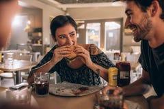 Женщина есть бургер с друзьями на ресторане Стоковое Изображение