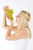 Женщина есть виноградины Стоковое Фото