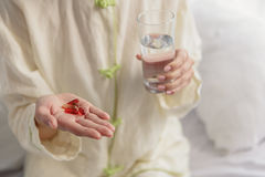 Женщина есть витамины и питьевую воду стоковые фото