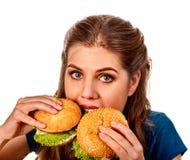 Женщина есть 2 гамбургера Укус девушки очень большого бургера стоковые изображения