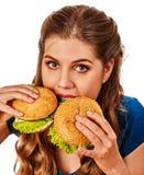 Женщина есть гамбургеры Портрет студента уничтожает фаст-фуд стоковая фотография