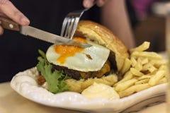 Женщина есть гамбургер мяса с ножом и вилкой стоковая фотография