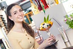 Женщина есть десерт в баре Стоковое Фото