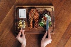Женщина есть зажаренный salmon стейк служила на деревянной доске с лимоном и салатом стоковое фото