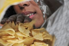 Женщина есть картофельные стружки Стоковое фото RF