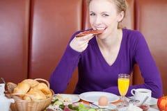 Женщина есть кусок хлеба с вареньем на таблице кафа Стоковые Фото