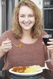 Женщина есть на вынос карри и выпивая вино Стоковое Изображение RF