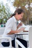 Женщина есть на таблице кафа Стоковое Изображение RF