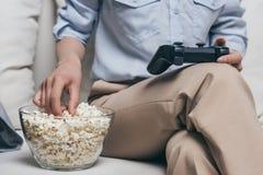 Женщина есть попкорн пока играющ видеоигры дома Стоковые Изображения RF