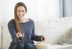 Женщина есть попкорн пока смотрящ ТВ Стоковые Фото