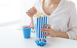 Женщина есть попкорн с питьем и конфетами стоковые изображения