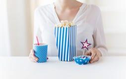 Женщина есть попкорн с питьем и конфетами стоковое фото rf