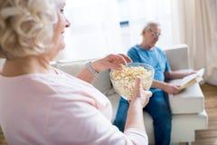 Женщина есть попкорн, человека сидя на софе и книгу чтения позади Стоковая Фотография