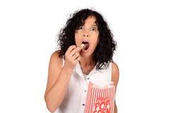 Женщина есть попкорн Стоковые Изображения