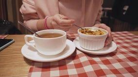 Женщина есть пудинг с яблоком, тыквой и апельсиновой коркой, выпивая чаем в кафе акции видеоматериалы