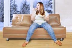 Женщина есть плиту donuts на кресле Стоковые Изображения RF