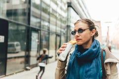 Женщина есть сандвич и идти стоковое изображение