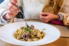 Женщина есть свежие очень вкусные макаронные изделия гриба в белой плите Стоковые Изображения