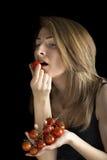 Женщина есть томаты вишни Стоковые Изображения RF